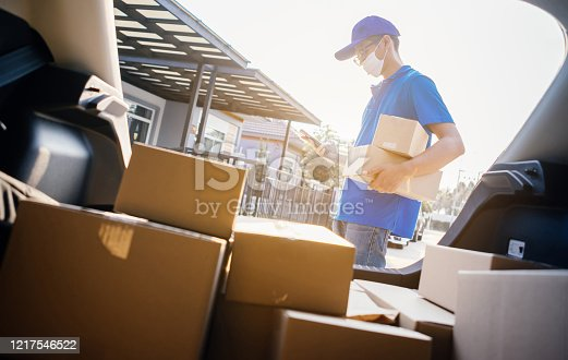 Asian Delivery man wearing mask send a package holding smartphone on front receiver shipping deliver cargo social distancing, Many parcel in trunk hatchback car while the virus is spreading.