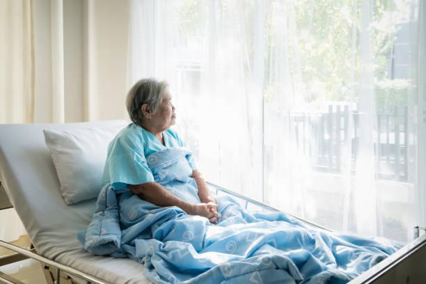 Asiatische deprimiert Seniorin Patienten am Bett schaut aus dem Fenster im Krankenhaus liegen. Ältere Frau Patienten ist froh, dass von der Krankheit erholt. – Foto
