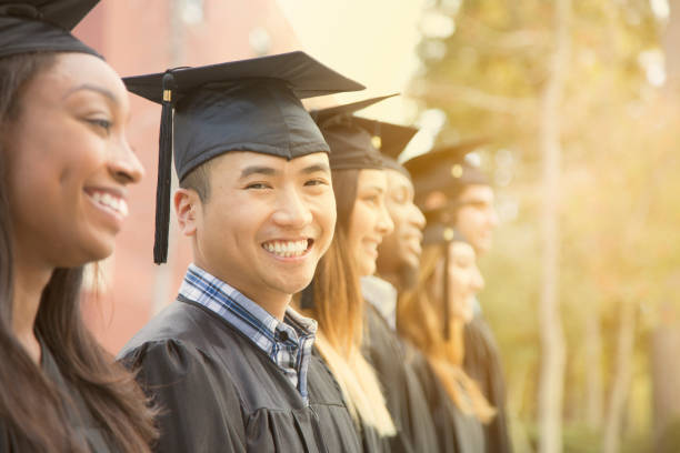 Asian descent male college student graduation on campus. stock photo