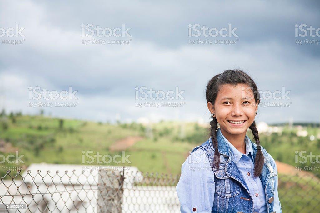 Asian descent, teenage girl posing on city street. stock photo