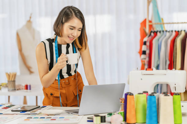 Asian designer woman working with computer laptop and multicolor chart at workplace