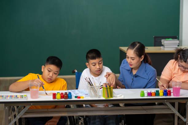 anak disabilitas asia dan seni belajar anak autisme di kelas dengan guru - child learn and work potret stok, foto, & gambar bebas royalti