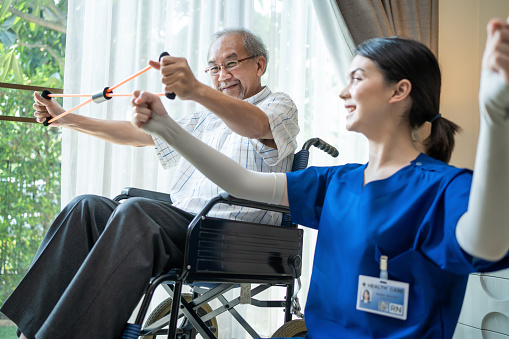 Asian Disabled senior elderly man on wheelchair doing physiotherapist with support from therapist nurse. Older handicapped man using resistance stretch band exercise for patient in home nursing care