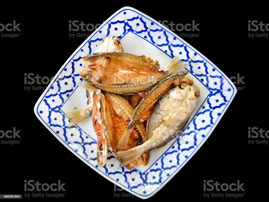 Asian Dish - Thai food: Deep fried salted sun drying fish served on tradiotnal thai style plate called 'Pla dad deaw tod' isolated on black background stock photo