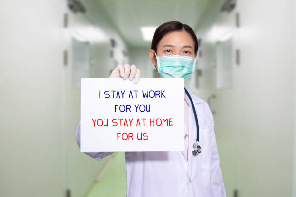 Asiatische Arzt im Krankenhaus tragen medizinische Masken, halten Papier mit Text I STAY AT WORK FOR YOU, YOU STAY AT HOME FOR US. Bei der Heimpolitik Kampagne zur Kontrolle der COVID-19 Coronavirus Ausbruch Situation – Foto