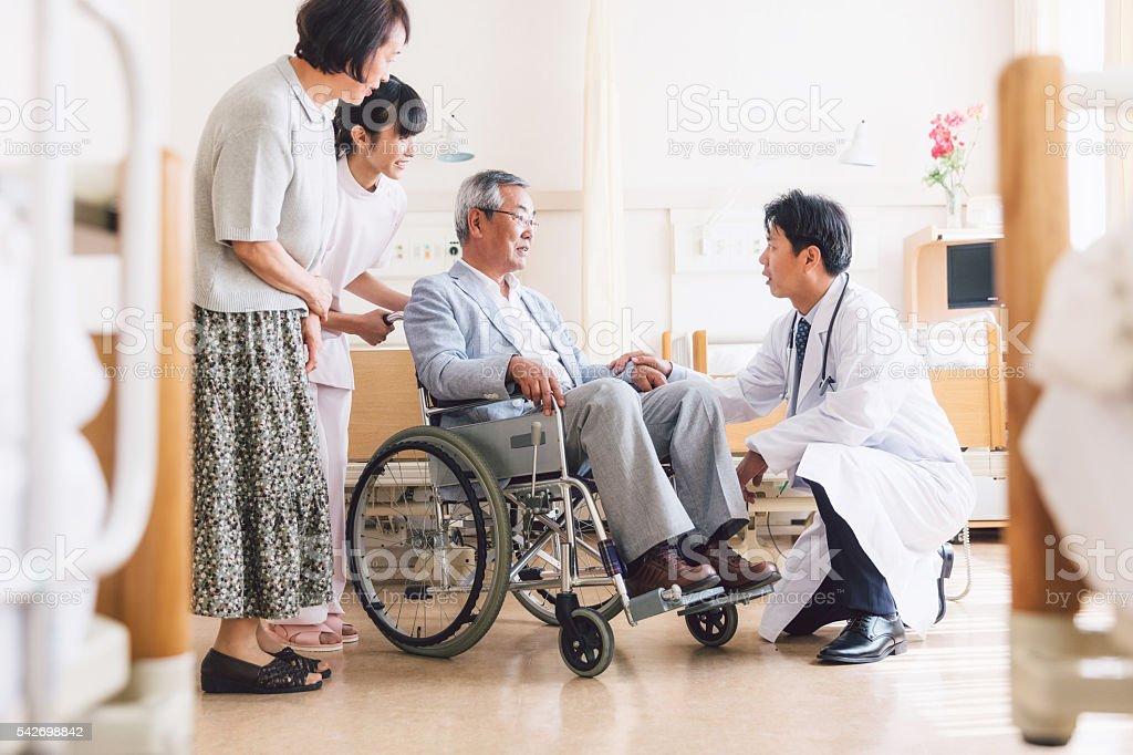 Asiatischen Arzt Besuch ein Patienten im Rollstuhl – Foto