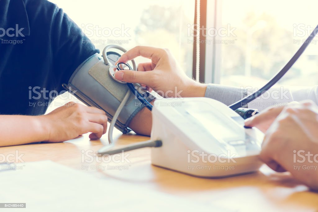 Asian doctor female measuring blood pressure of male patient at clinic office room. stock photo