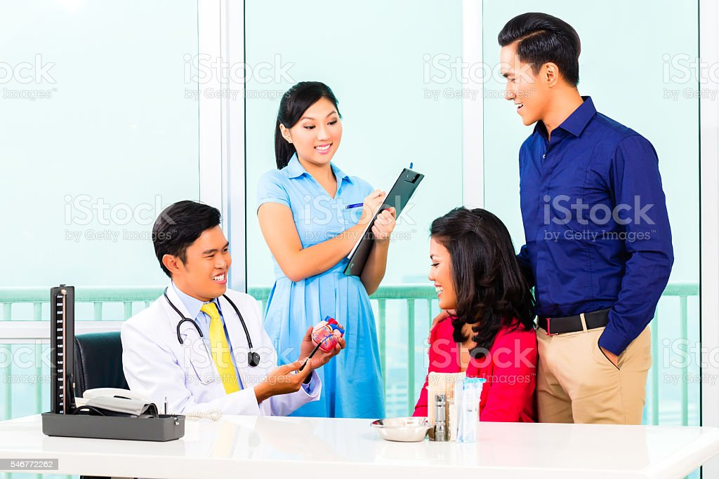Asian doctor giving heart patient advice stock photo