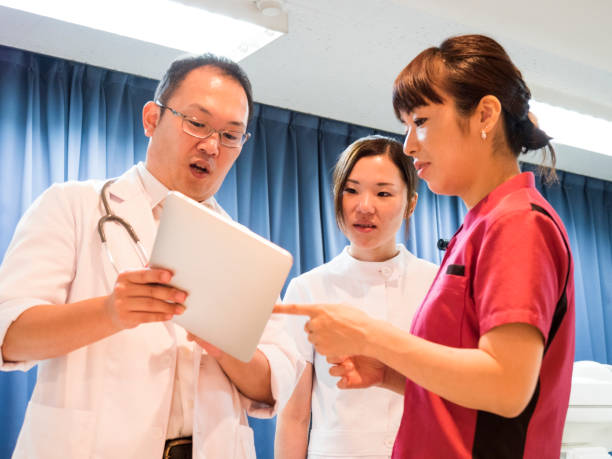 Asian doctor showing digital tablet to nurse in hospital stock photo