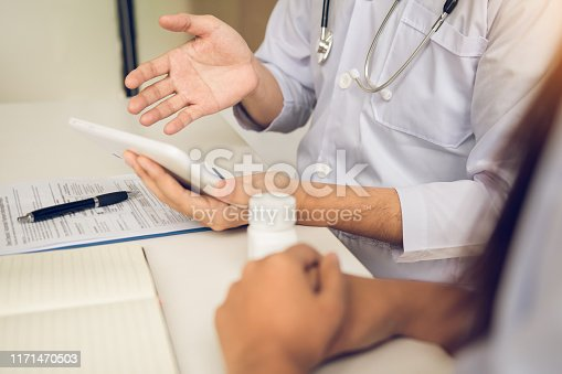 873418972istockphoto Asian doctor talking the patient at clinic while using the tablet explaining the patient condition and the treatment result. 1171470503