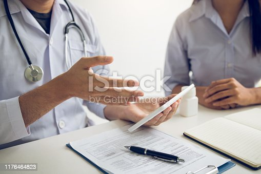 873418972istockphoto Asian doctor talking the patient at clinic while using the tablet explaining the patient condition and the treatment result. 1176464823