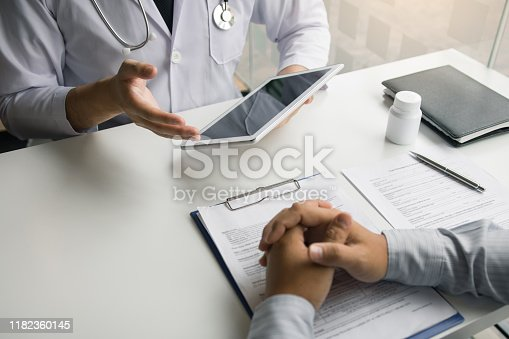 873418972istockphoto Asian doctor talking the patient at clinic while using the tablet explaining the patient condition and the treatment result. 1182360145