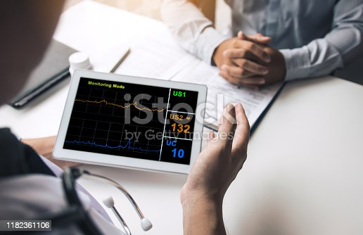 873418972istockphoto Asian doctor talking the patient at clinic while using the tablet explaining the patient condition and the treatment result. 1182361106