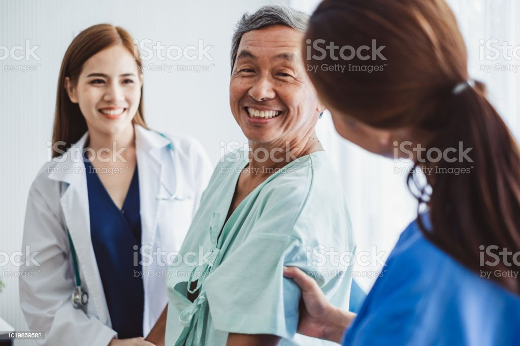 Asian doctor woman and nurse encourage disabled old man patient sitting on wheelchair at hospital, asian medical concept stock photo