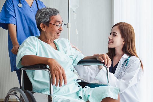 504241549 istock photo Asian doctor woman and nurse encourage disabled old man patient sitting on wheelchair at hospital, asian medical concept 1034818382