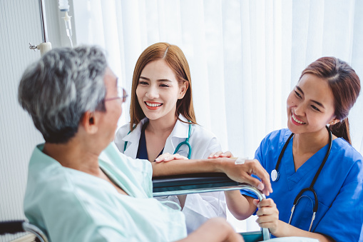 504241549 istock photo Asian doctor woman and nurse encourage disabled old man patient sitting on wheelchair at hospital, asian medical concept 1034818824