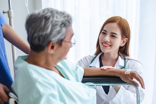 504241549 istock photo Asian doctor woman and nurse encourage disabled old man patient sitting on wheelchair at hospital, asian medical concept 1034821444