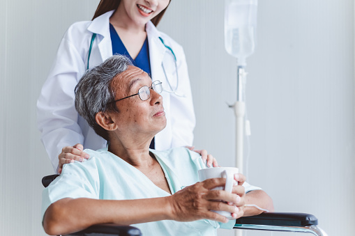 504241549 istock photo Asian doctor woman encourage disabled old man patient sitting on wheelchair at hospital, asian medical concept 1019859810