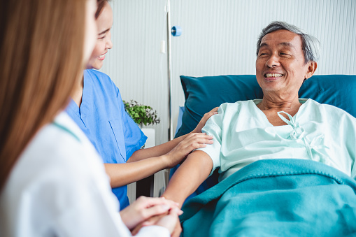 504241549 istock photo Asian doctor woman encourage disabled old patient by holding hand 1049772170