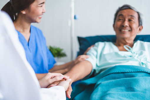 504241549 istock photo Asian doctor woman encourage disabled old patient by holding hand 1049772266