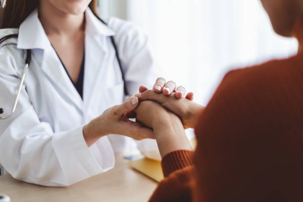 asian doctor woman encourage young woman patient by holding hand - cancer patient stock pictures, royalty-free photos & images