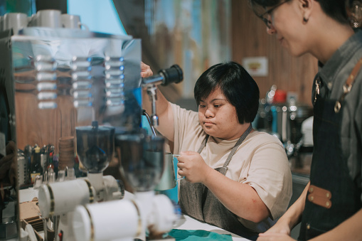 asian down syndrome female learning from barista making coffee in her café place of work