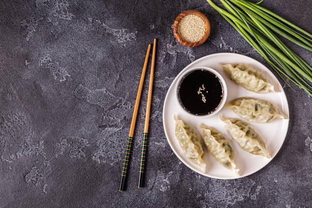 asiatische teigtaschen, sojasauce und stäbchen - knödel kochen stock-fotos und bilder