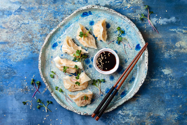 Asian dumplings with soy sauce, sesame seeds and microgreens. Traditional chinese dim sum dumplings. Copy space, flat lay Asian dumplings with soy sauce, sesame seeds and microgreens. Traditional chinese dim sum dumplings. Copy space, flat lay asian food stock pictures, royalty-free photos & images