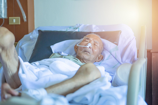 1049772134 istock photo Asian elder man sick and have tube in hospital ward,sleep in coma state on bed 1171646471