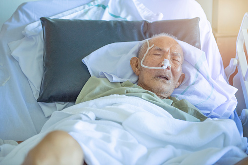 1049772134 istock photo Asian elder man sick and have tube in hospital ward,sleep in coma state on bed 1171646474