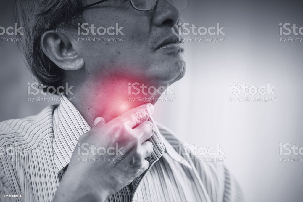 Asian elder old man Sore throat irritation and have a phlegm hand touching neck. stock photo