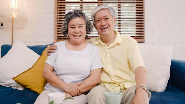 Asiatische ältere Paar gefühl glücklich lächelnd und Blick auf die Kamera, während auf dem Sofa im Wohnzimmer zu Hause entspannen. Genießen Sie Zeit Lifestyle Senior Familie zu Hause Konzept. Porträt mit Blick auf die Kamera. – Foto