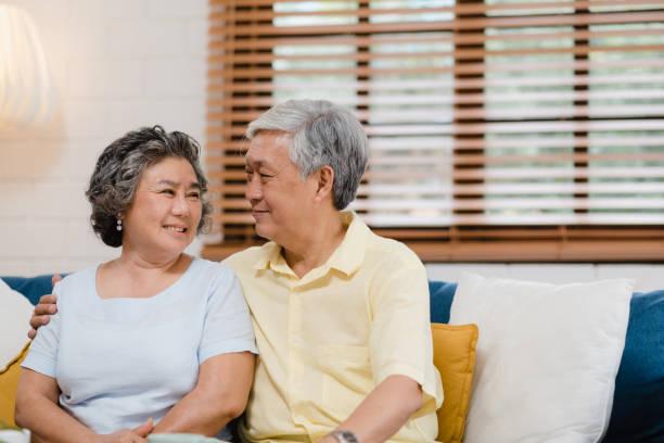 Asiatische ältere Paar halten ihre Hände, während sie zusammen im Wohnzimmer, Paar fühlen sich glücklich teilen und unterstützen einander auf dem Sofa zu Hause liegend. Lifestyle Senior Familie zu Hause Konzept. – Foto