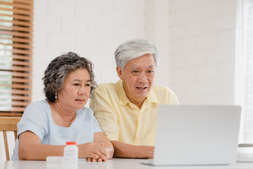 istock Asian elderly couple using laptop conference with doctor about medicine information in living room, couple using time together while lying on sofa at home. Senior family health at home concept. 1138393981