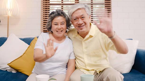 Asiatische ältere Paar mit Smartphone-Video-Konferenz mit Enkelkind, während auf dem Sofa im Wohnzimmer zu Hause liegen. Genießen Sie Zeit Lifestyle Senior Familie zu Hause Konzept. Porträt mit Blick auf die Kamera. – Foto