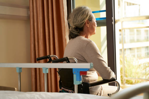asian elderly woman sitting in front of window in nursing home stock photo