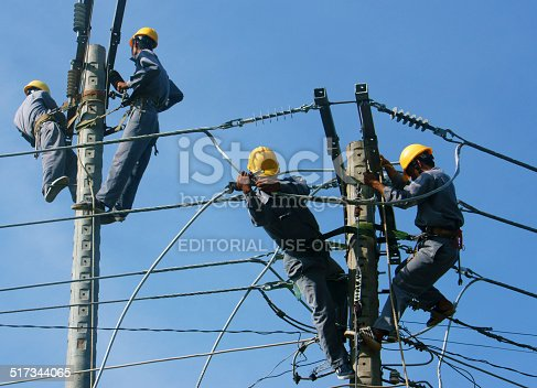 istock Asian electrician climb high, work on electric pole 517344065