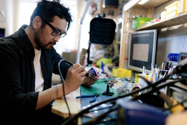 Asian electrician soldering in his studio stock photo