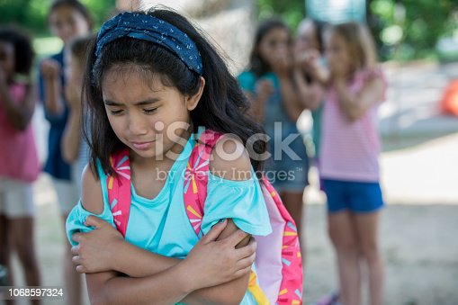 Elementary age Asian little girl is crying outside of school on playground. Diverse classmates are teasing and bullying her.