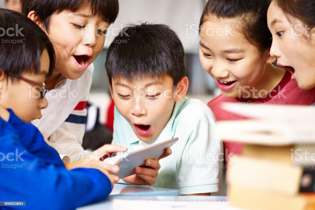 asian elementary school children playing with digital tablet during break stock photo