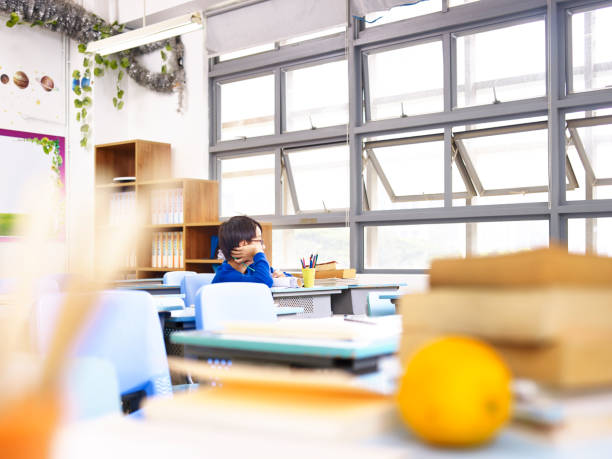 asian elementary school student sitting alone in classroom - boy looking out window stock pictures, royalty-free photos & images