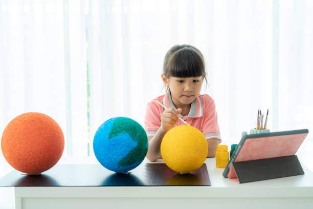 asian elementary schoolgirl painting the moon in science class learning about the solar system via video conference with teacher and other classmates at home, homeschooling and distance learning. - teacher school solo imagens e fotografias de stock
