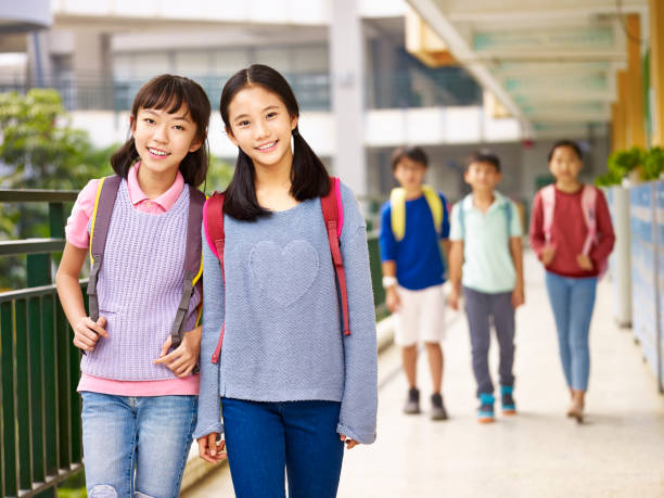 asian elementary schoolgirl walking in school asian elementary school girls walking in corridor in classroom building. japanese school girl stock pictures, royalty-free photos & images