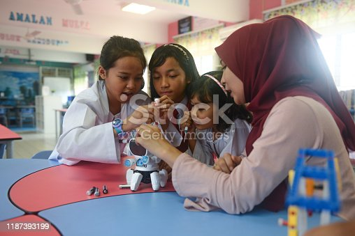 Asian elementary schoolgirls and female teacher building robot in science class