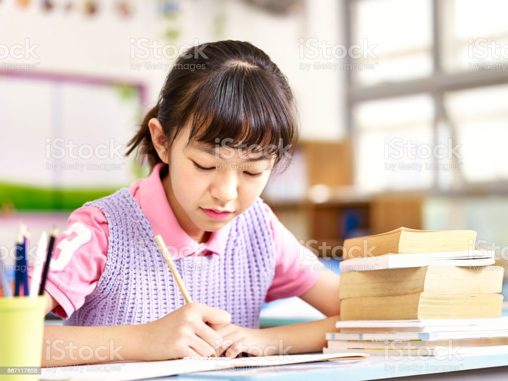 Asian Elementary Student Studying In Classroom Royalty Free Stock Photo