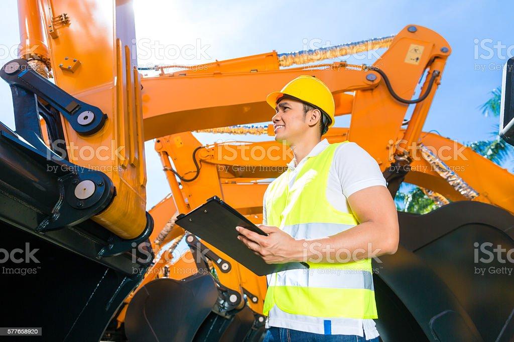 Asian engineer controlling shovel excavator stock photo