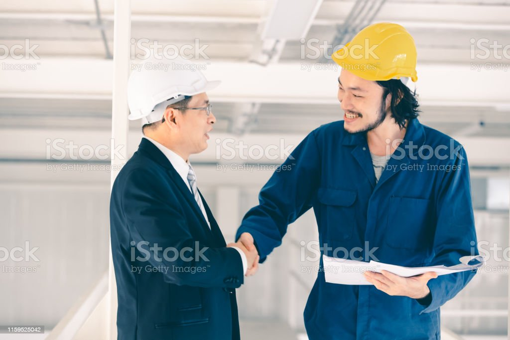 Young Asian engineer handshakes with executive engineer in industrial...