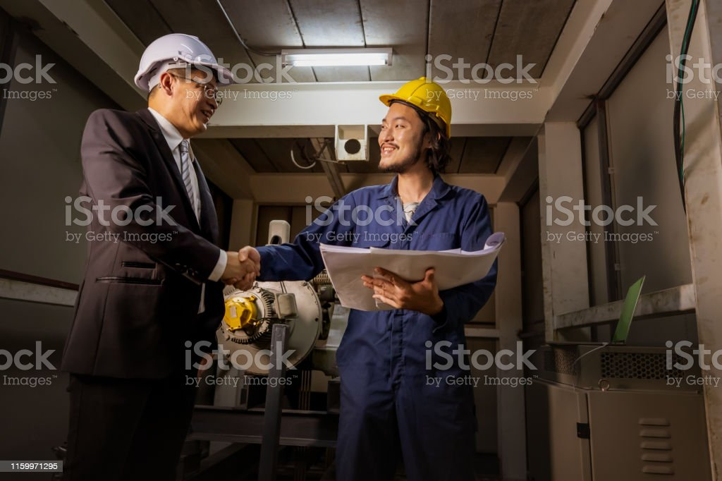 Young Asian engineer handshakes with executive engineer beside heavy...