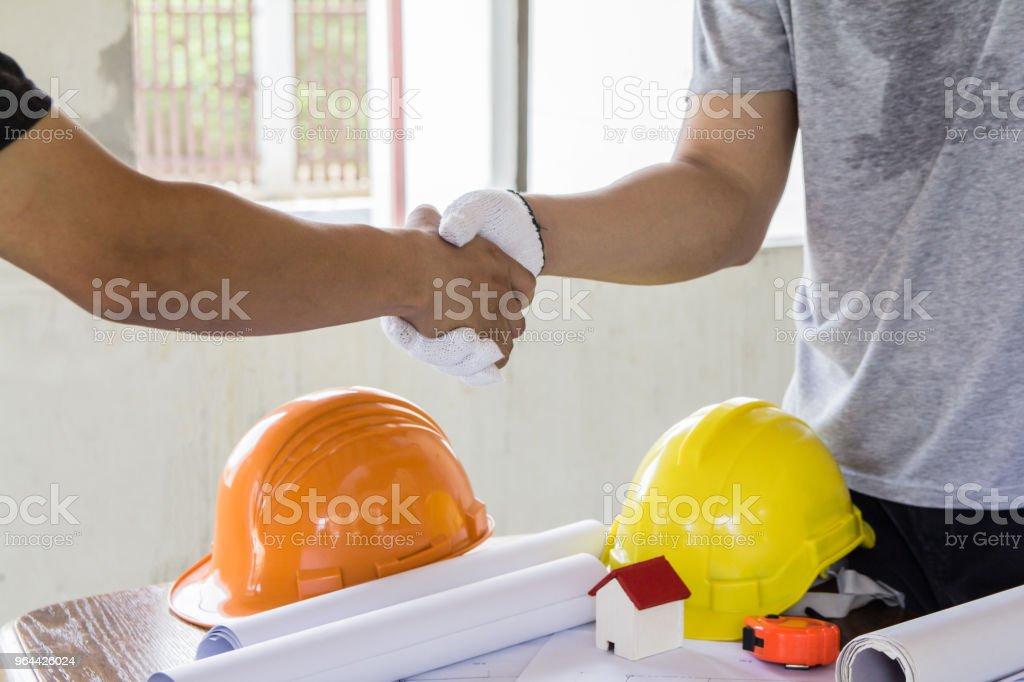 Aziatische ingenieur handshaking voor teamwork in interieur-ontwerp en constructie-plan. Concept van de architect - Royalty-free Apparatuur Stockfoto