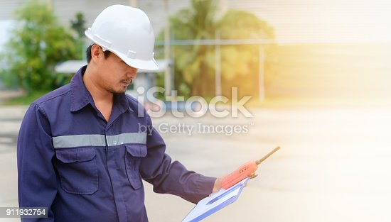 istock Asian engineer in safety uniform and white helmet holding a clipboard and walkie-talkie on blurred industry plant background with sun light effect for industrial concept 911932754